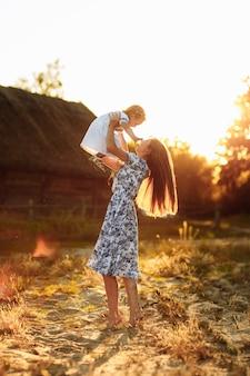 Moeder speelt met haar dochtertje, jonge gelukkige en leuke vrouw die geniet van en speelt met haar dochter van het babymeisje die haar omhoog houdt in haar armen lachend.