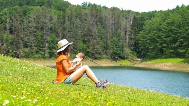 Moeder speelt met haar pasgeboren zoon in een meer met pijnbomen eromheen en prachtige bloemen