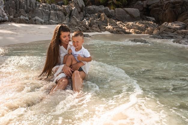 Moeder speelt met haar zoon in de oceaan