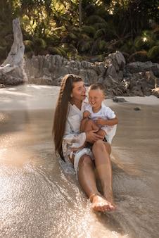 Moeder speelt met haar zoon in de oceaan.
