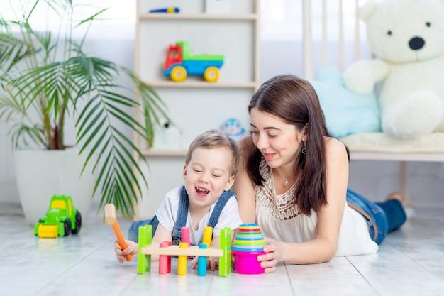 Moeder speelt met het kind thuis in het educatieve speelgoed in de kinderkamer. een gelukkig, liefdevol gezin.