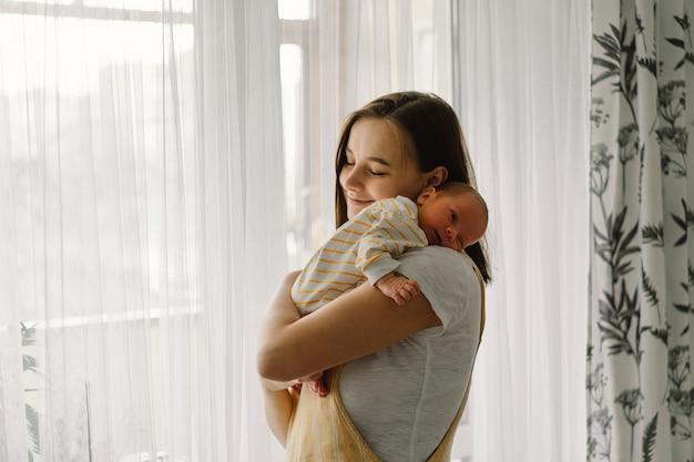 Moeder speelt met pasgeboren zoontje thuis in de buurt van het raam. gelukkige baby en moeder.