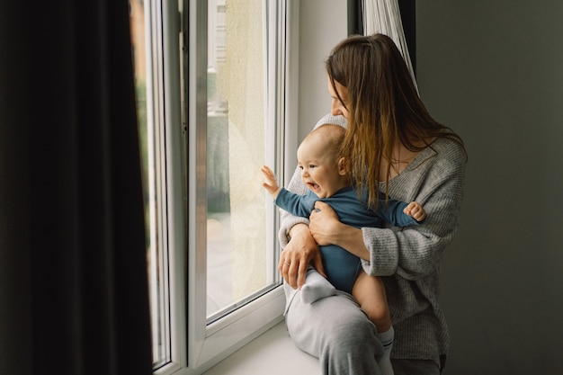 Moeder speelt met zoontje thuis in de buurt van het raam. gelukkige baby en moeder.