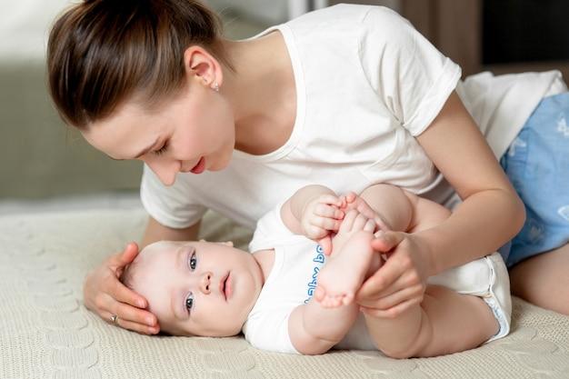 Moeder speelt thuis met de baby 6 maanden op het bed