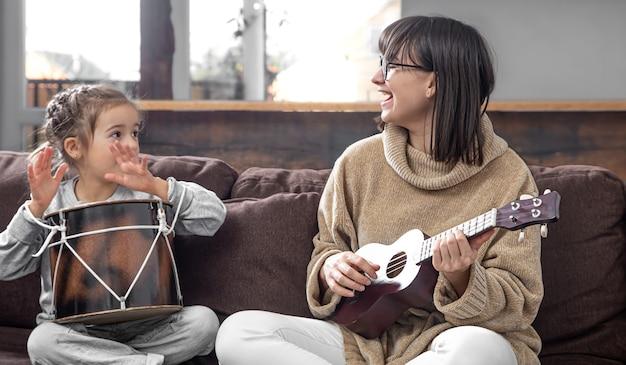 Moeder speelt thuis met haar dochter. lessen over een muziekinstrument. ontwikkeling en gezinswaarden van kinderen. het concept van vriendschap en familie van kinderen.