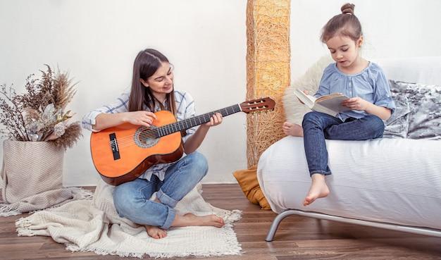 Moeder speelt thuis met haar dochters. lessen over een muziekinstrument, gitaar. het concept van vriendschap en familie van kinderen.