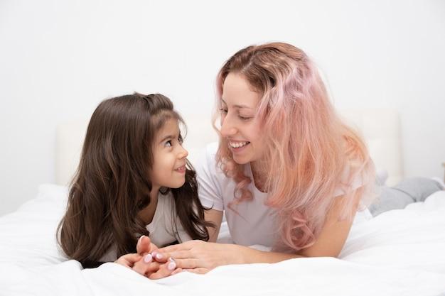Moeder spelen met actieve dochtertje in bed thuis, plezier, activiteit met kinderen.