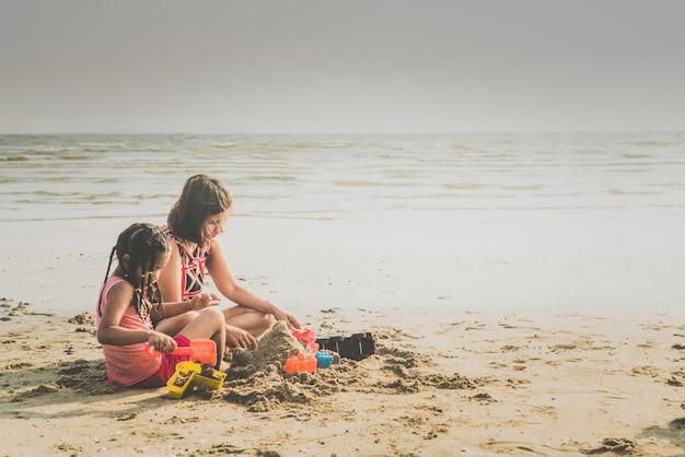 Moeder spelen met kinderen op het strand vreugdevol