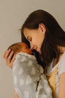Moeder spelen met pasgeboren zoontje thuis. gelukkige baby en moeder.
