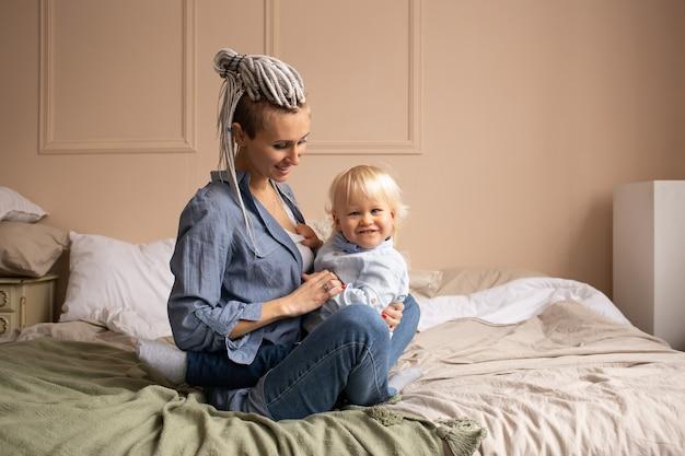 Moeder spelen met zoon thuis op bed. gelukkige familie plezier thuis