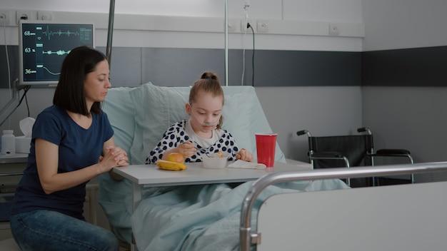 Moeder staat met ziek meisje terwijl ze tijdens de lunch gezond voedsel eet, wachtend op medische deskundige...