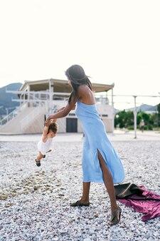 Moeder staat op het strand en zwaait klein meisje bij de armen