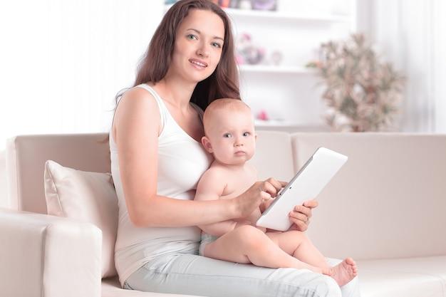 Moeder toont de babyfoto's op een digitale tablet. mensen en technologie