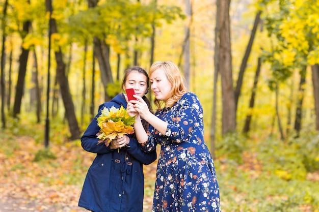 Moeder toont haar tienermeisjesfoto's op mobiele telefoon buiten in de herfstnatuur.