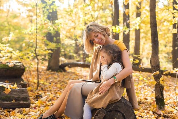 Moeder troost haar huilende kleine meisje in de herfst, natuuremoties en familieconcept