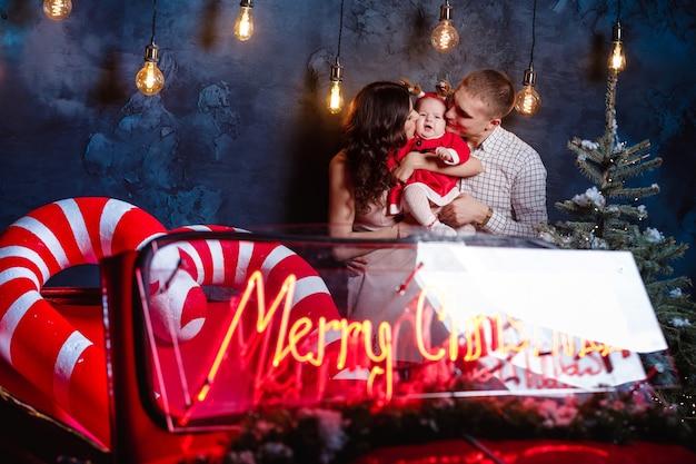 Moeder, vader en babymeisje met plezier in de buurt van kerstboom en retro rode auto. ouders met een dochtertje in een kerstfotosessie. studio-opnamen voor de feestdagen.
