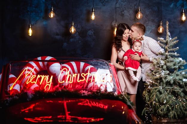 Moeder, vader en babymeisje met plezier in de buurt van kerstboom en retro rode auto. studio-opnamen voor de feestdagen.