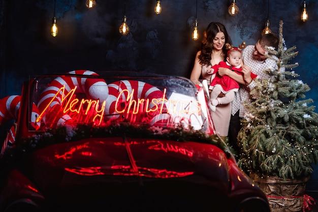 Moeder, vader en babymeisje met plezier in de buurt van kerstboom en retro rode auto.