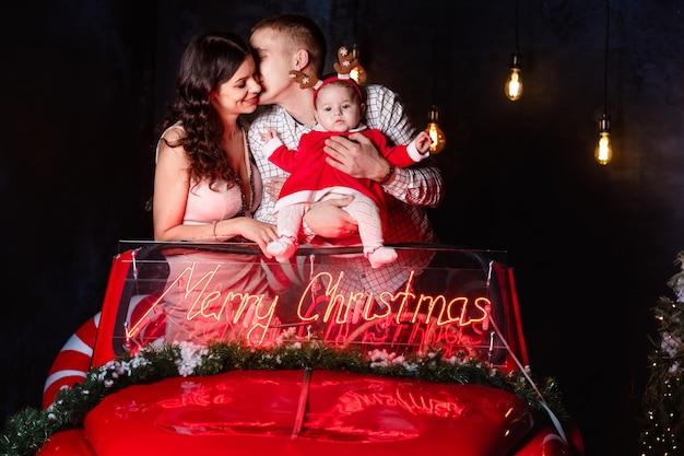 Moeder, vader en babymeisje met plezier in de kerst retro rode auto. ouders met een dochtertje in een kerstfotosessie.