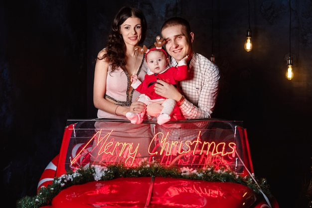 Moeder, vader en babymeisje met plezier in de retro rode kerstauto met kerstversiering