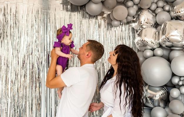 Moeder, vader en babymeisje op een grijze vakantieachtergrond met ballons. de vader tilt het kind op