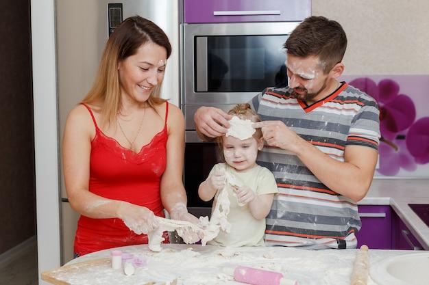 Moeder, vader en dochter die deeg thuis keuken maken