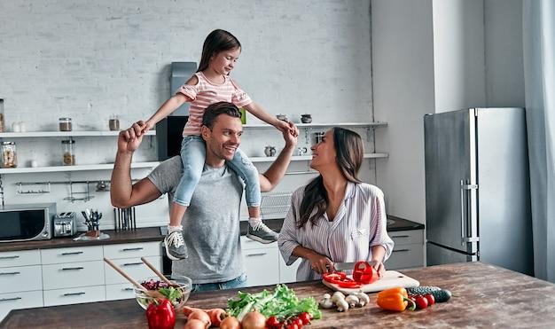 Moeder, vader en dochter koken in de keuken. gelukkig gezin concept. knappe man, aantrekkelijke jonge vrouw en hun schattige dochtertje maken samen salade. gezonde levensstijl.