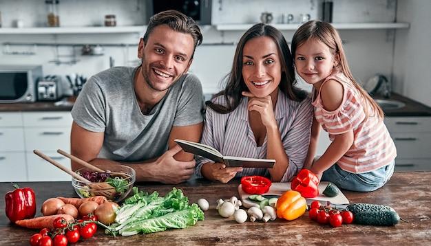Moeder, vader en dochter koken in de keuken met receptenboek. gelukkig gezin concept. knappe man, aantrekkelijke jonge vrouw en hun schattige dochtertje maken samen salade. gezonde levensstijl.