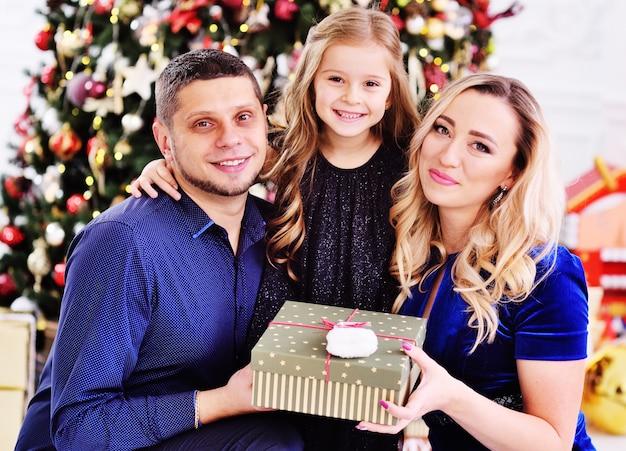 Moeder, vader en dochtertje knuffelen met een geschenk in hun handen op de achtergrond van een kerstboom.