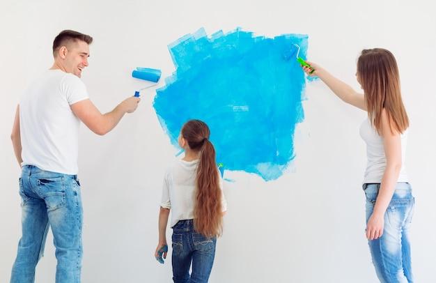 Moeder, vader en dochtertje schilderen de muur in hun nieuwe huis.