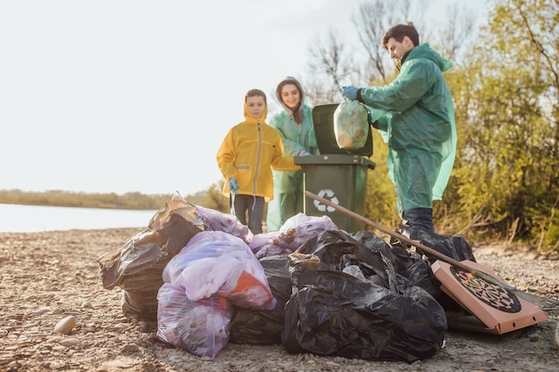 Moeder, vader en dson met groep vrijwilligers die afval op het strand oppakken.