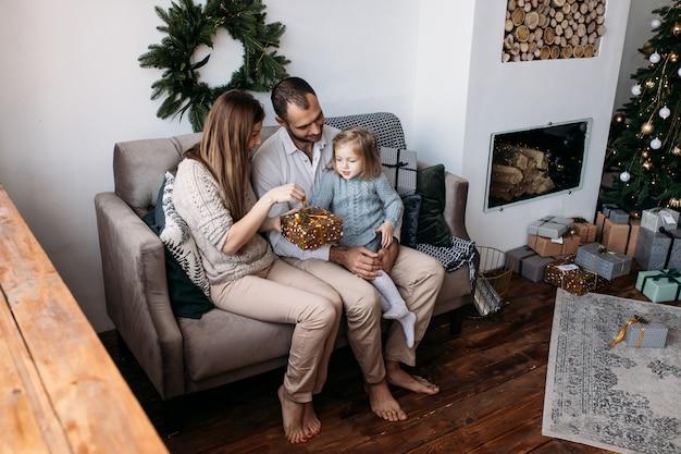 Moeder, vader en hun schattige dochter die kerstcadeaus uitwisselen
