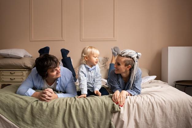 Moeder, vader en kind met plezier in de slaapkamer. mensen die thuis ontspannen. familie liggend op bed.