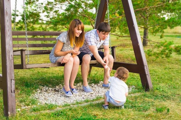 Moeder, vader en kind zoon samen buiten spelen.