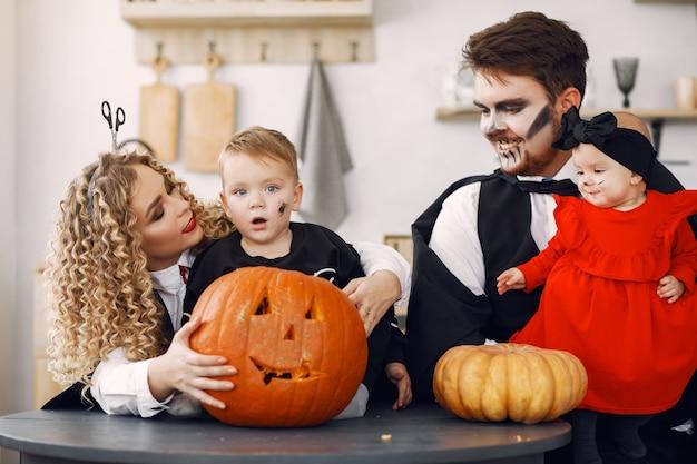 Moeder vader en kinderen in kostuums en make-up. familie bereidt zich voor op de viering van halloween.