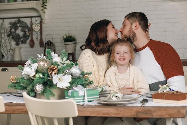 Moeder, vader en mooie dochter aan de keukentafel