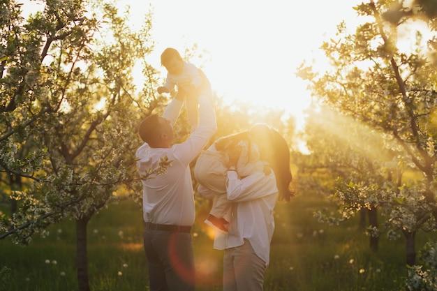 Moeder vader en twee dochter in de natuur bij zonsondergang
