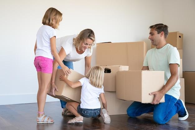 Moeder, vader en twee dochters met kartonnen dozen in de woonkamer