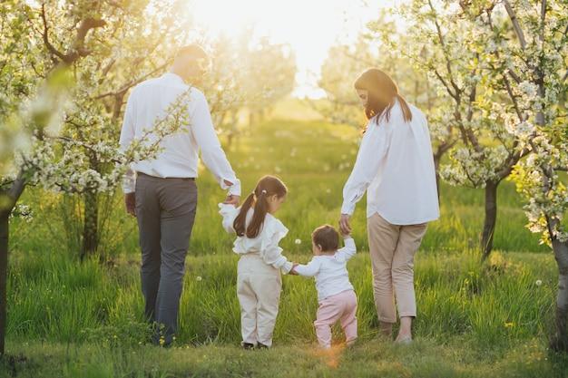 Moeder vader en twee dochters wandelen in de natuur