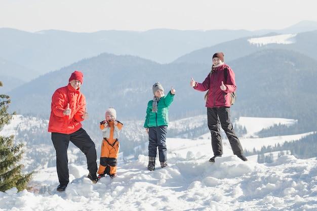 Moeder, vader en twee zonen staan en glimlachen tegen de achtergrond van met sneeuw bedekte bergen.