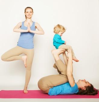 Moeder, vader en zoon doen yoga over witte ruimte