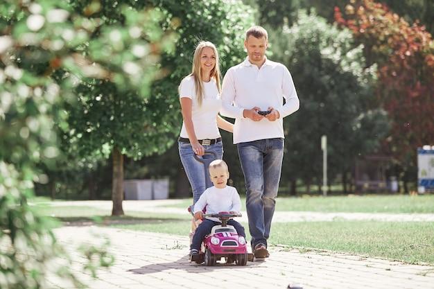 Moeder, vader en zoon lopen over een pad in een stadspark