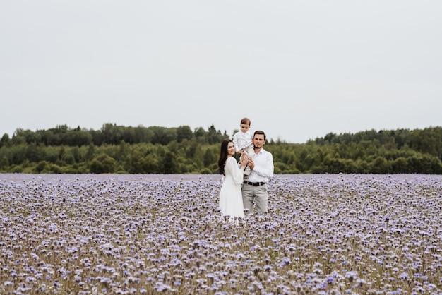 Moeder, vader en zoon op de achtergrond van een bloeiend paars veld