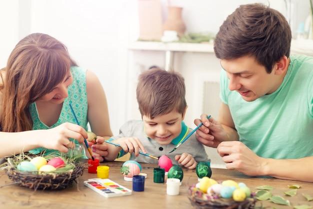 Moeder, vader en zoon schilderen eieren. gelukkige familie bereiden zich voor op pasen.