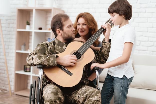 Moeder vader en zoon zingen met een gitaar.