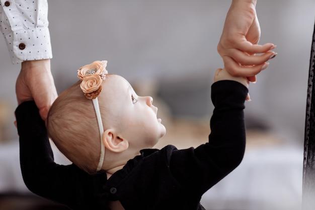 Moeder, vader houden handen dochter geniet samen thuis van tijd. bekijk de benen. moederdag, vaderdag, baby's dag. concept van jonge familievakantie en zorg voor liefde en ondersteuning voor de volgende generatie.