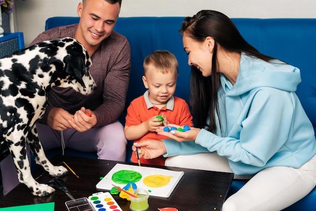 Moeder, vader, zoon en hun hond spelen thuis met plasticine en verf
