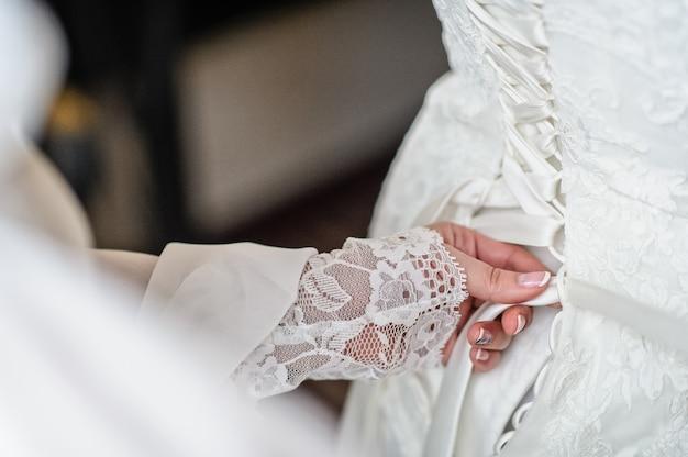 Moeder van de bruid helpt de trouwjurk te binden