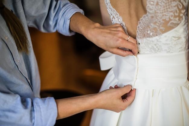 Moeder van de bruid helpt haar te kleden