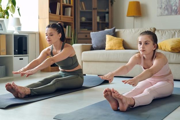 Moeder van middelbare leeftijd en haar tienerdochterzitting op oefeningsmatten en het uitrekken zich benen in woonkamer